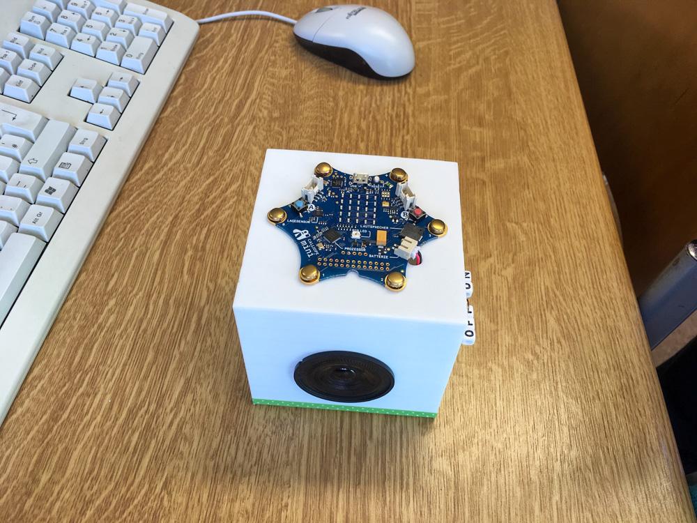 Foto: ein Würfel mit elektronischen Bauelementen an der Seite auf eine Tisch neben einer Tastatur