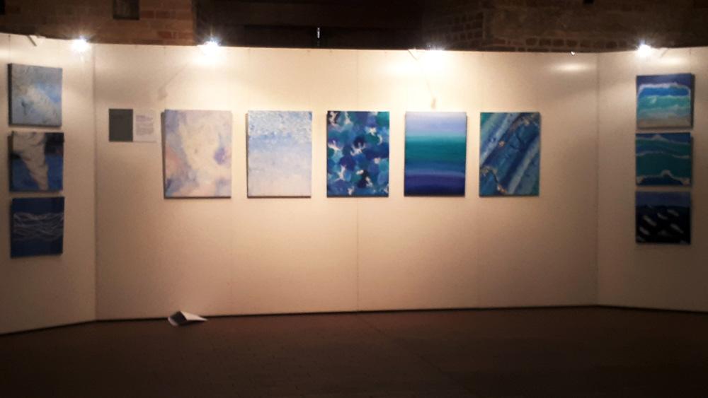 Foto: Bilder einer Ausstellung an einer Wand