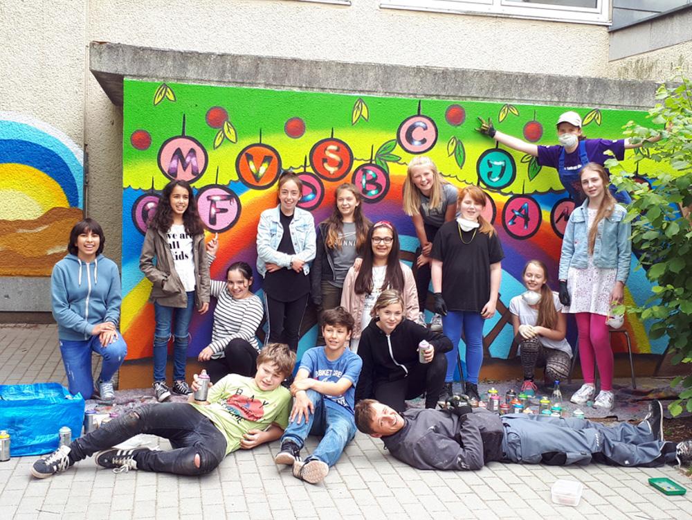 Foto: mehrere Jugendliche stehen und liegend vor eine bunt besprayten Hauswand