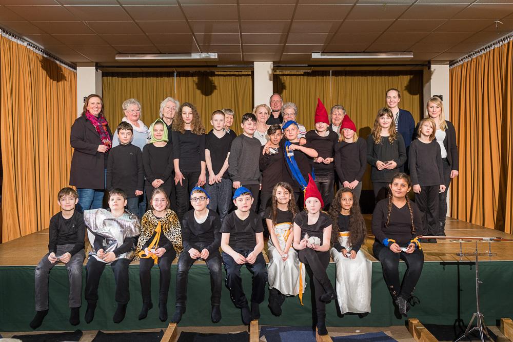 Foto: Erwachsene und Kinder auf eine Bühne zum Gruppenfoto positioniert