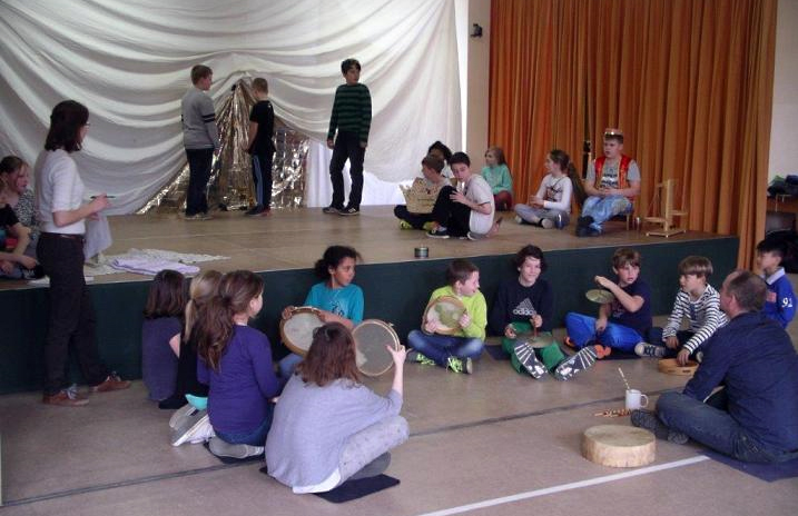 Kinder und 2 Erwachsene vor und auf eine Bühne bei Theaterproben