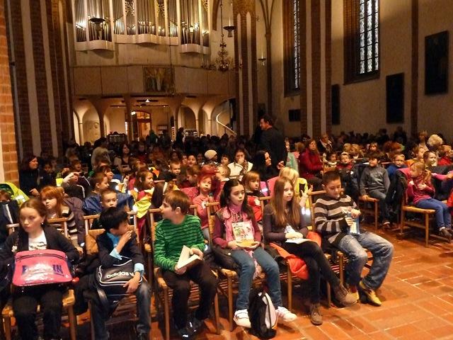 Foto: Kinder sitzen auf Stuhlreihen in einer Kirche