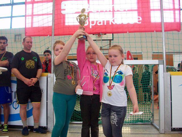 Foto: 3 Mädchen halten gemeinsam einen Pokal in die Höhe