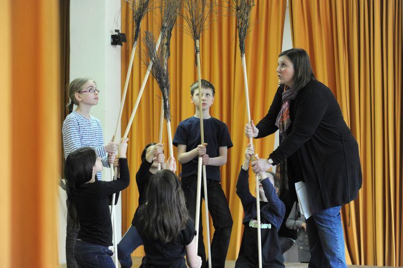 Foto: Kinder und eine Frau mit Reisigbesen in der Hand bei Theaterproben
