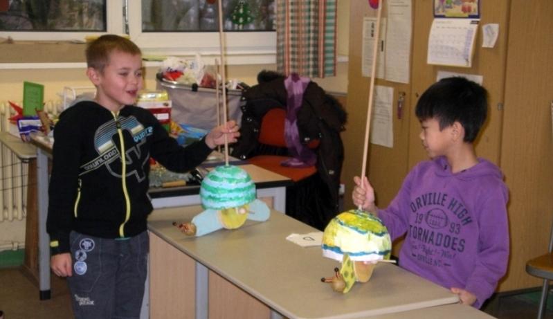 Foto: 2 Jungs halten ihre selbstgebastelten Rennschnecken in der Hand auf einem Tisch