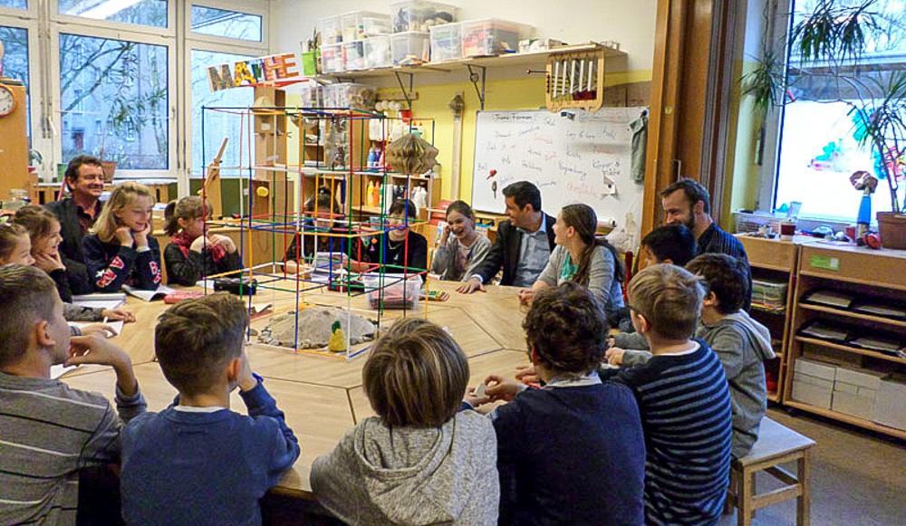 Foto: Kinder und Erwachsene sitzen an einen große runden Tisch mit einer Konstruktion darauf