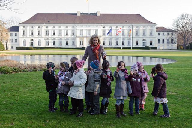 Foto: Kinder mit Seifenblasendosen geschart um eine Frau. Im Hintergrund Schlossgebäude.