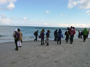 Foto: Menschen beim Strandspaziergang am Meer