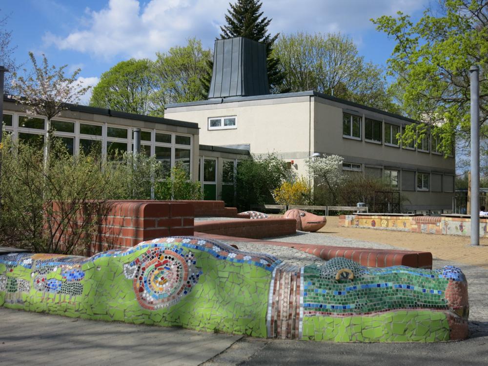 Foto: Schulhof mit gestaltete Mosaik-Sitzbänken aus Beton