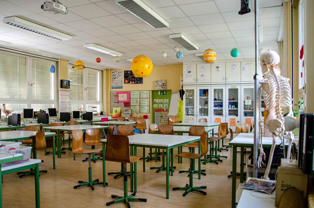 Foto: Klassenraum mit Stühlen und Tischen und Gerippemodel im Vordergrund
