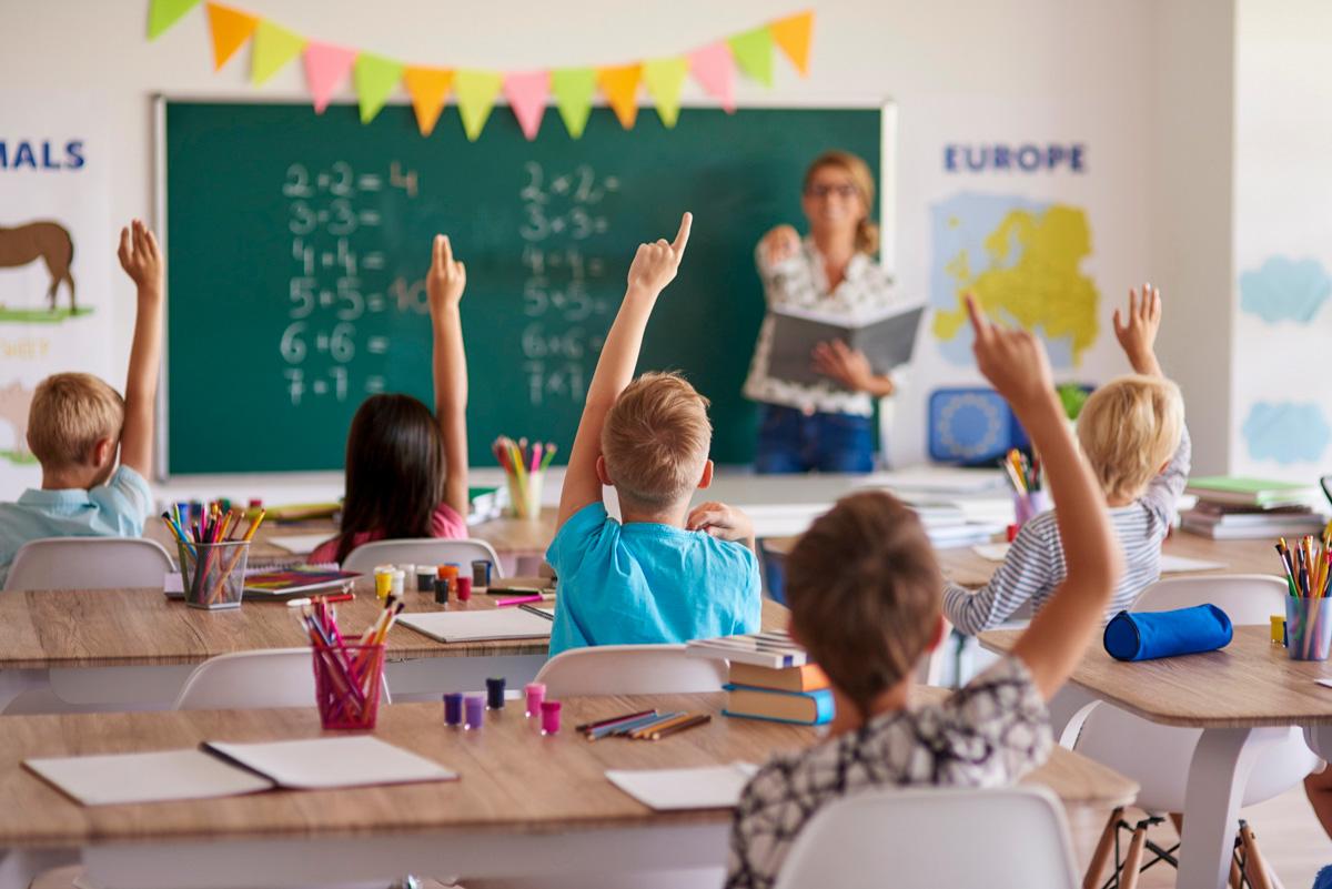 Foto: Kinder mit ausgestecktem Arm sitzen am Schulbank in einem Klassenraum. An der Tafel Lehrerin.